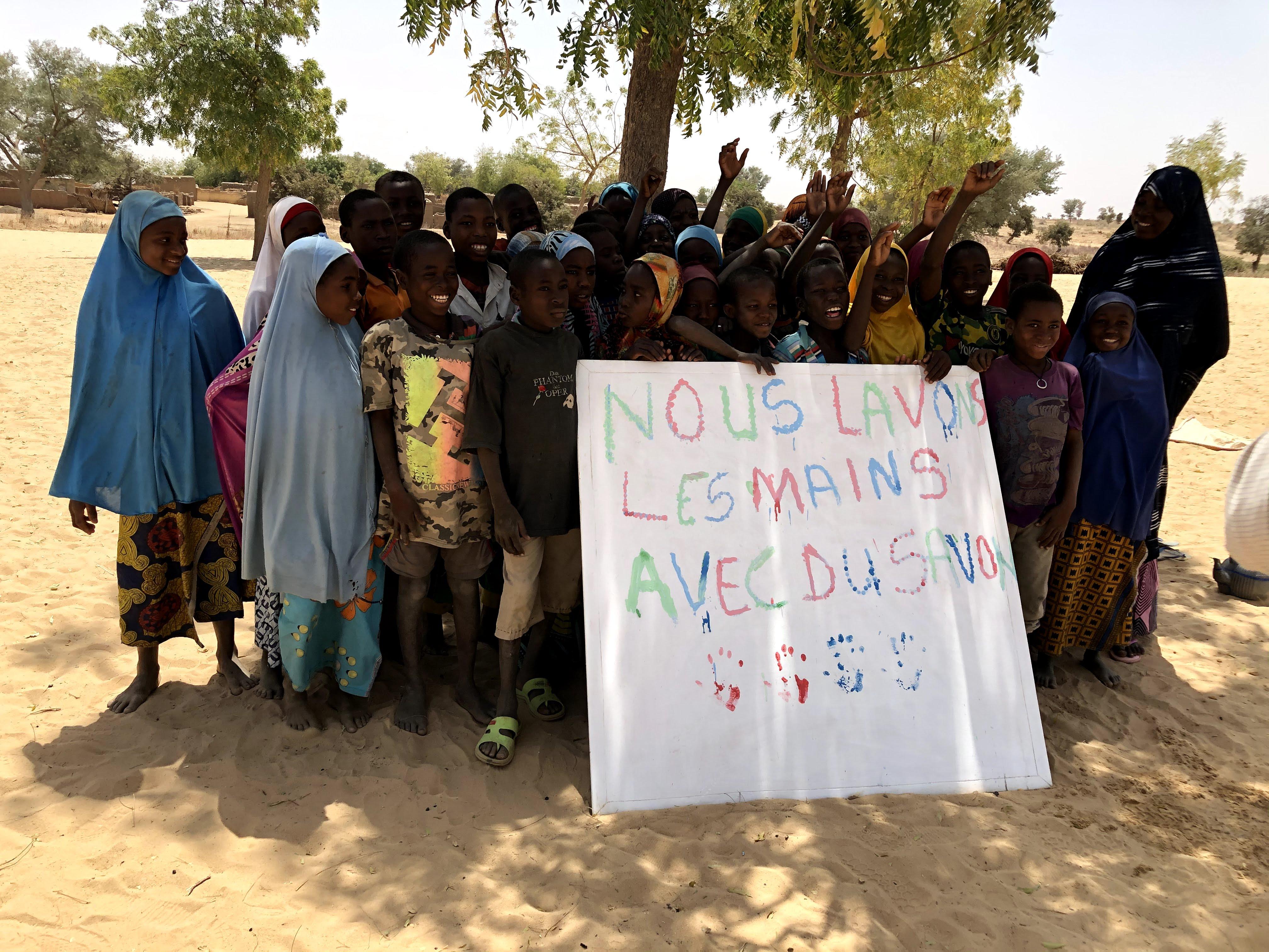 Børn med et skilt hvorpå der står: 'Vi vasker vores fingre med sæbe'