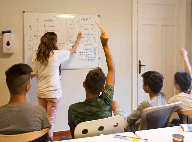 Teacher teaching Greek to refugee youths